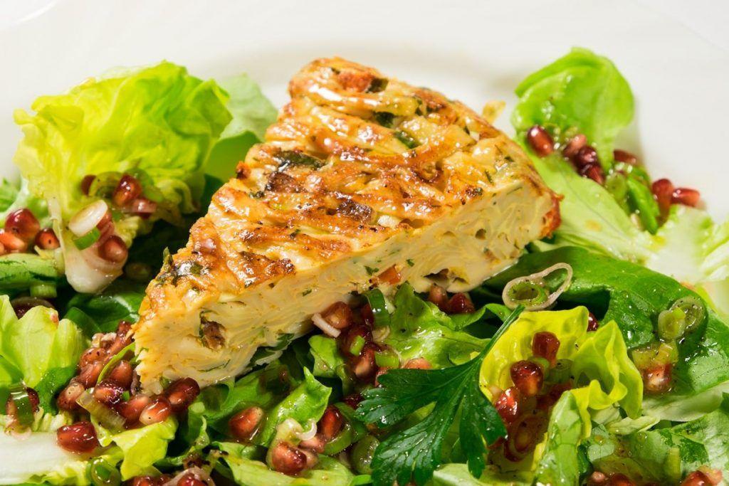 Nudeltorte auf Salat mit Granatapfel