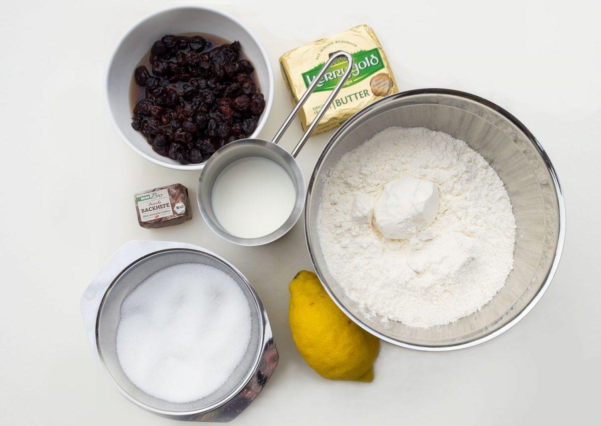 Zutaten für eine Zitronenbäbe, Butter, Zitrone, Mehl, Milch, Rosinen und Hefe