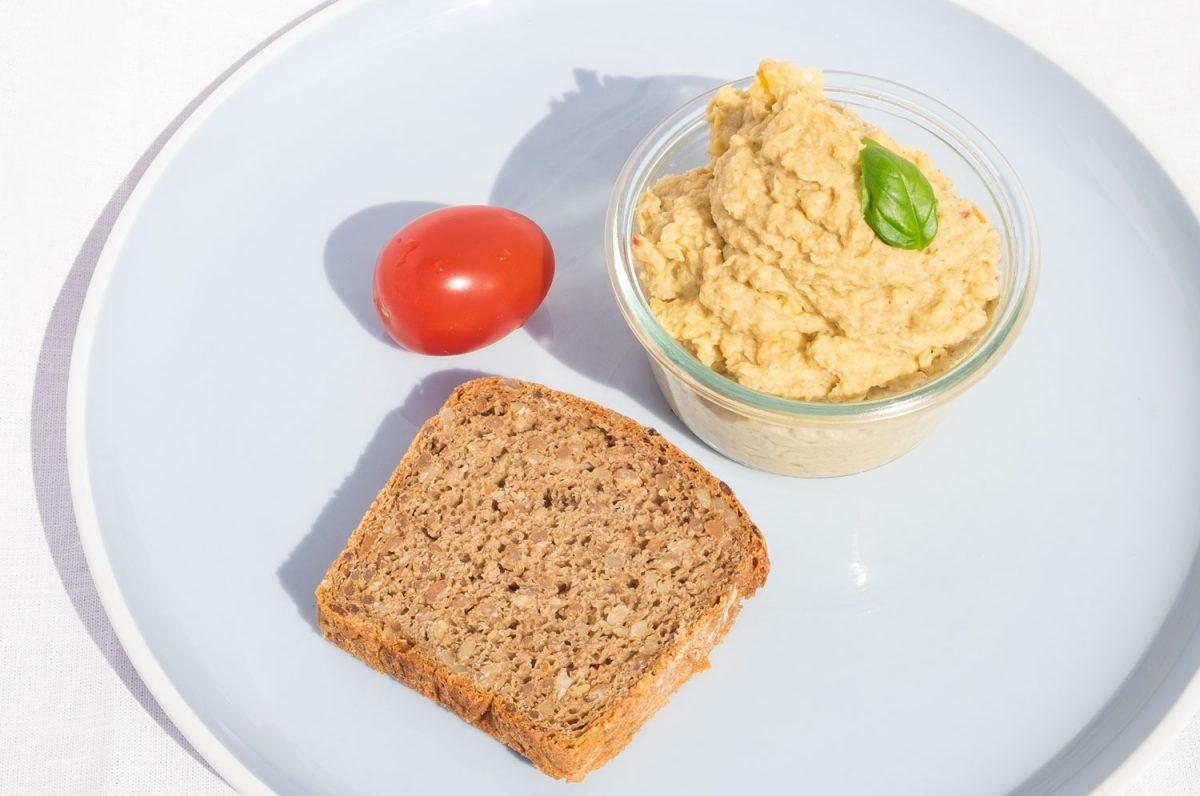 Hummus mit Salzzitrone und Roggen-Vollkorn-Brot auf dem Teller