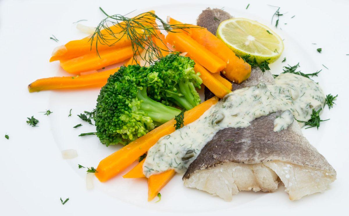 Gekochter Kabeljau mit Gemüse auf einem Teller